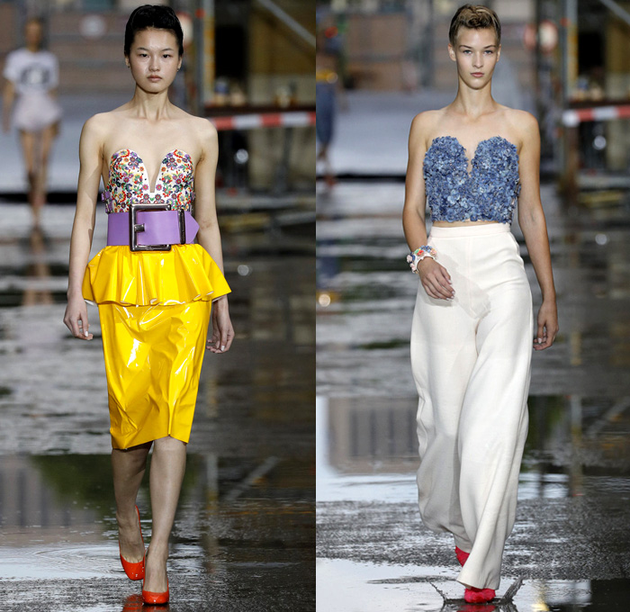 Marina Hoermanseder 2018 Spring Summer Womens Runway Catwalk Looks - Berlin Fashion Week Germany Deutschland Frühjahr Sommer 2018 - Matryoshka Russian Nesting Babushka Doll Mega Buckle Wide Belt Sculptural Straps Wrap Around Bustier Corset Strapless PVC Vinyl Pleather Bedazzled Metallic Studs Denim Jeans Sheer Chiffon Organza Tulle Turtleneck Sweater Jumper Shirt Crop Top Midriff Tiered Ruffles Flounce Flowers Floral Botanical Embroidery Belt Skirt Miniskirt Peplum Wide Leg Trousers Palazzo Pants Leotard Thigh High Boots Headscarf Tote Handbag